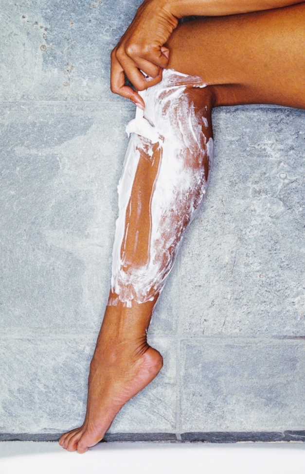 woman shaving legs with shaving cream and razor